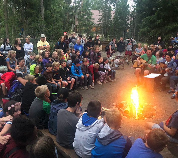 Camp fire, group of people listening to man playing guitar.