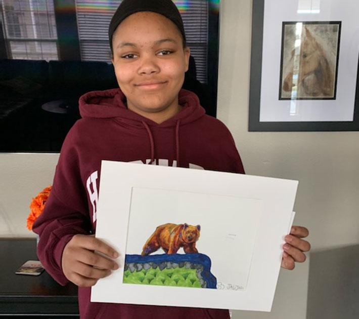 Child holding art.