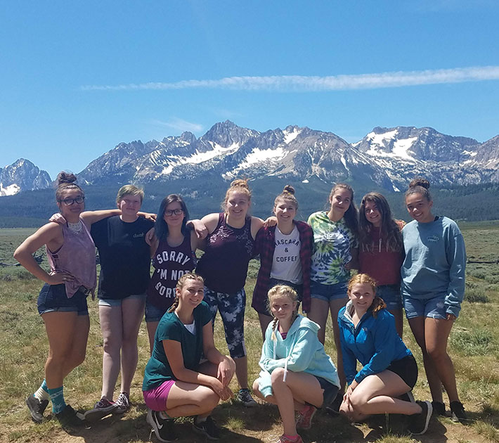 Girls in front of a mountain.