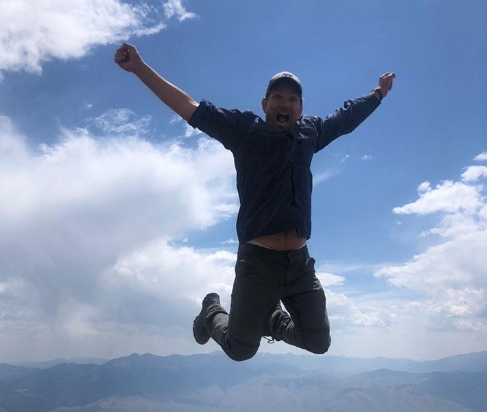 Man jumping in air on top of mountain - K Alan Bean
