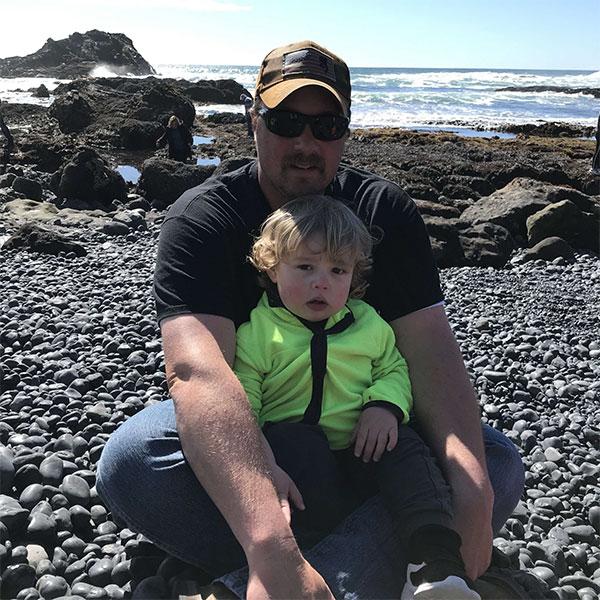 Matt Goodfellow sitting on beach with child